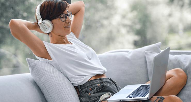 Uma mulher deitada bem relaxada em um sofá, com um notebook no colo.